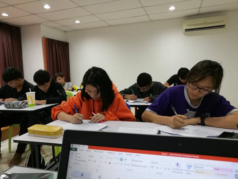 This is an image referring to a group of IGCSE students in a IGCSE centre preparing for their Chinese paper. This IGCSE Chinese tuition prepares students for their Foreign and Second Language Chinese for IGCSE. Their IGCSE Chinese tutor will be guiding them in terms of reading, speaking, listening and writing. For Foreign Language, they will need to cover 4 papers. In contrast, Second Language there will be only 3 papers. There are few students also doing online tuition for their IGCSE Chinese subject.