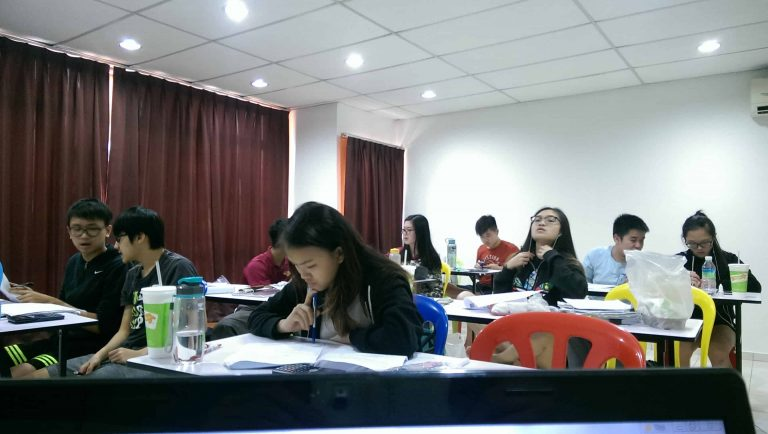 Students preparing for their exam in TWINS Education's igcse ict tuition. Their ICT tutors are giving them exam papers to practice.